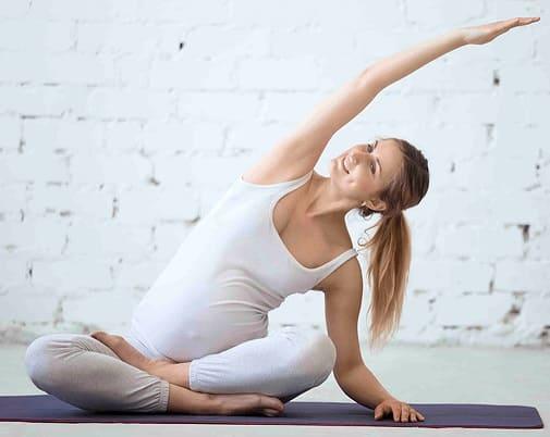 Беременная сидя делает наклоны