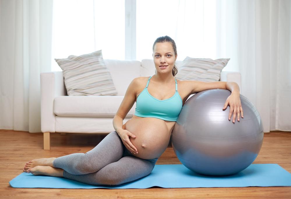 Беременная рядом с мячом