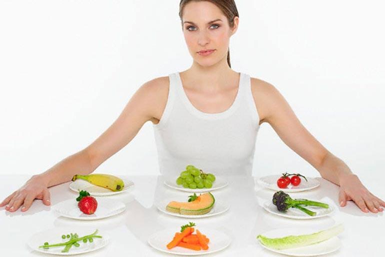 Женщина перед столом со здоровой пищей