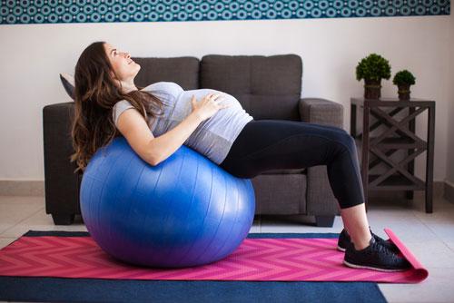 Беременная спиной лежит на фитболе