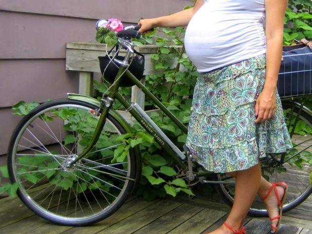 Беременная с велосипедом рядом с домом
