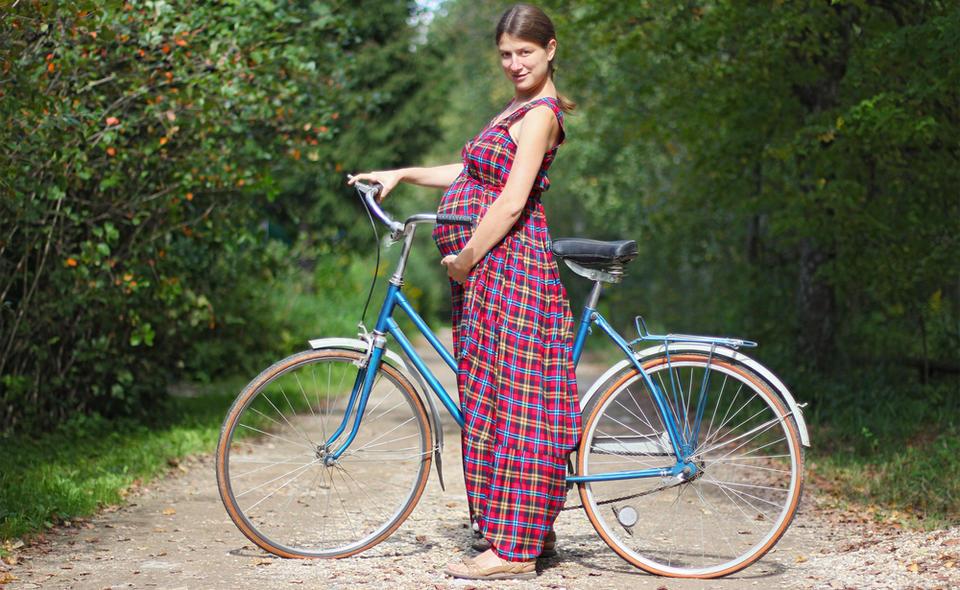 Беременная с велосипедом в парке