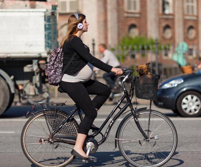 Беременная на велосипеде в городе
