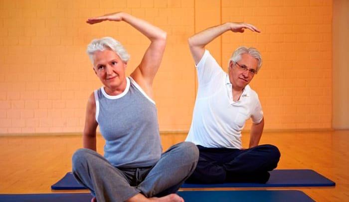 Пожилая пара делает гимнастику