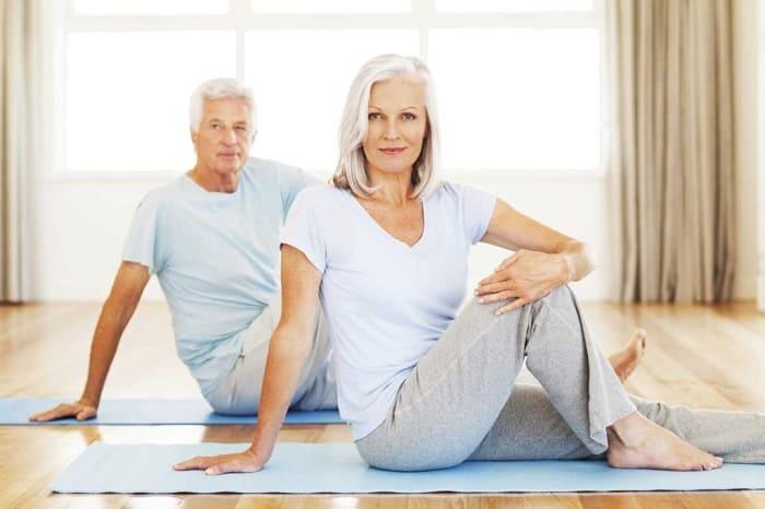 Пожилая пара на ковриках делает упражнения