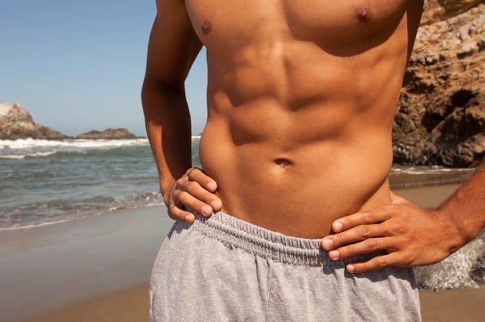Пресс с кубиками мужчины на пляже