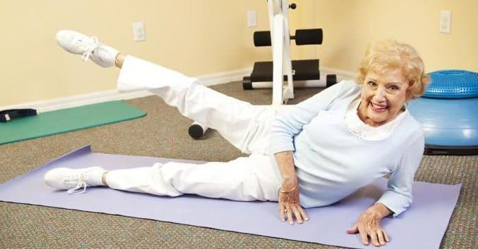 Пожилая женщина делает гимнастику