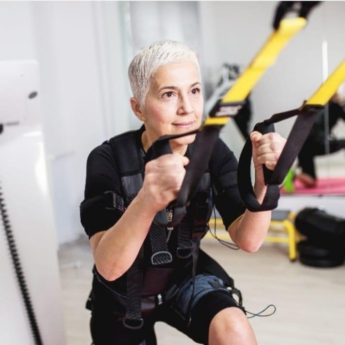 Женщина 50+ в спортзале занимается с TRX